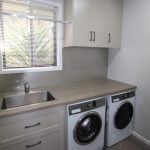 Laundry cabinetry with drawers and hanging rail.
