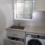 Laundry cabinet with a drawer below the sink